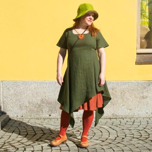 Vihreä pellavainen mekko, jossa epäsymmetrinen kaunis liehuva helma ja lyhyet hihat