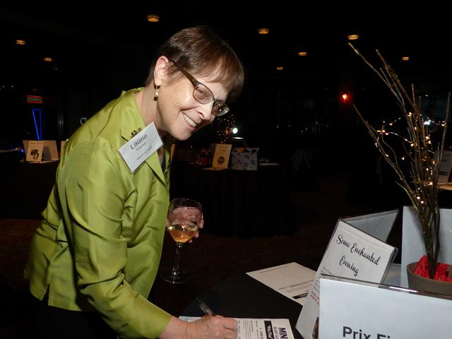 Chief revenue officer Laurie Kramer bidding on a silent auction item