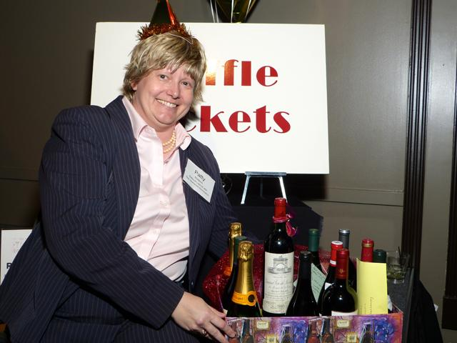 Patty Mattern displaying the treasure trove of wine she won in the raffle