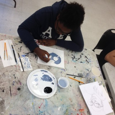 Mint Artists Guild summer staff started their work by painting a self portrait. Alexis Bagley works intently on hers.