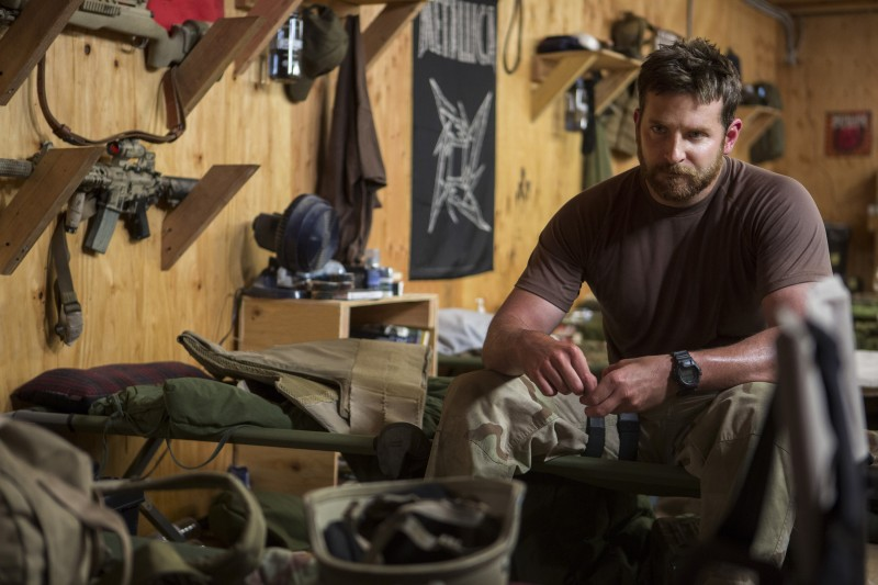 """In this image released by Warner Bros. Pictures, Bradley Cooper appears in a scene from """"American Sniper"""" as sniper Chris Kyle. He is sitting on a cot wearing military fatigues and a dark t-shirt. He is surrounded by military gear, with rifles mounted nearby on the wall.  (AP Photo/Warner Bros. Pictures, Keith Bernstein)"""
