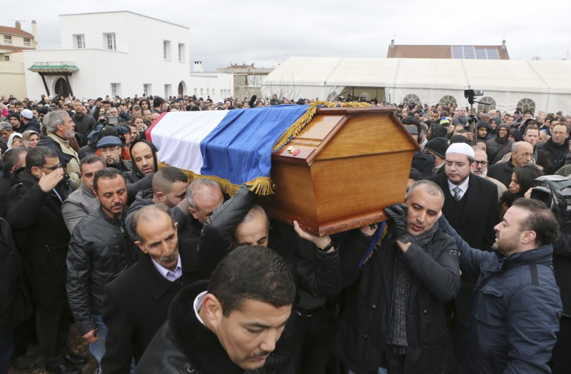 People carry the coffin of slain police officer Ahmed Merabet after a funeral service at the Bobigny Mosque, east of Paris, France, Tuesday, Jan. 13, 2015.  While both the Kouachi Brothers' killings and Lubitz's deliberate crash of the Germanwings flight were brutal tragedies, media treatment of each has been noticeably different. (AP Photo/Jacques Brinon)