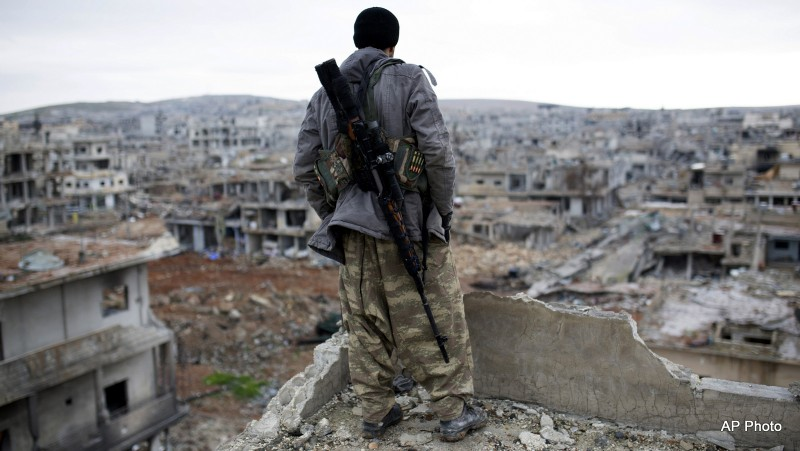File: A Syrian rebel sniper looks at the rubble in the Syrian city of Ain al-Arab. on Jan. 30, 2015.