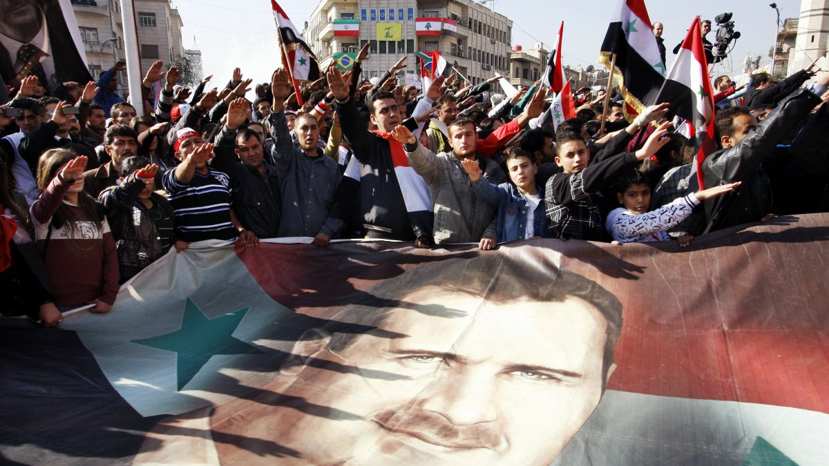 "FILE - In this Monday, Dec. 19, 2011 file photo, Syrians hold a large poster depicting Syria's President Bashar Assad during a rally in Damascus, Syria. Some activists expressed regret that one year later their ""revolution"" against President Bashar Assad's rule had become mired in violence. (AP Photo/Muzaffar Salman, File)"