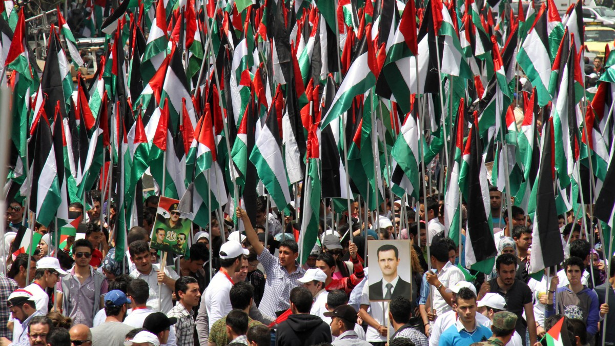 Pro-Syrian government demonstrators hold Baath party flags and a picture of President Bashar Assad at a rally at Sabe Bahrat Square to commemorate the 65th anniversary of the foundation of the Ruling Baath Arab Socialist Party in Damascus, Syria, Saturday, April 7, 2012. (AP Photo Bassem Tellawi)