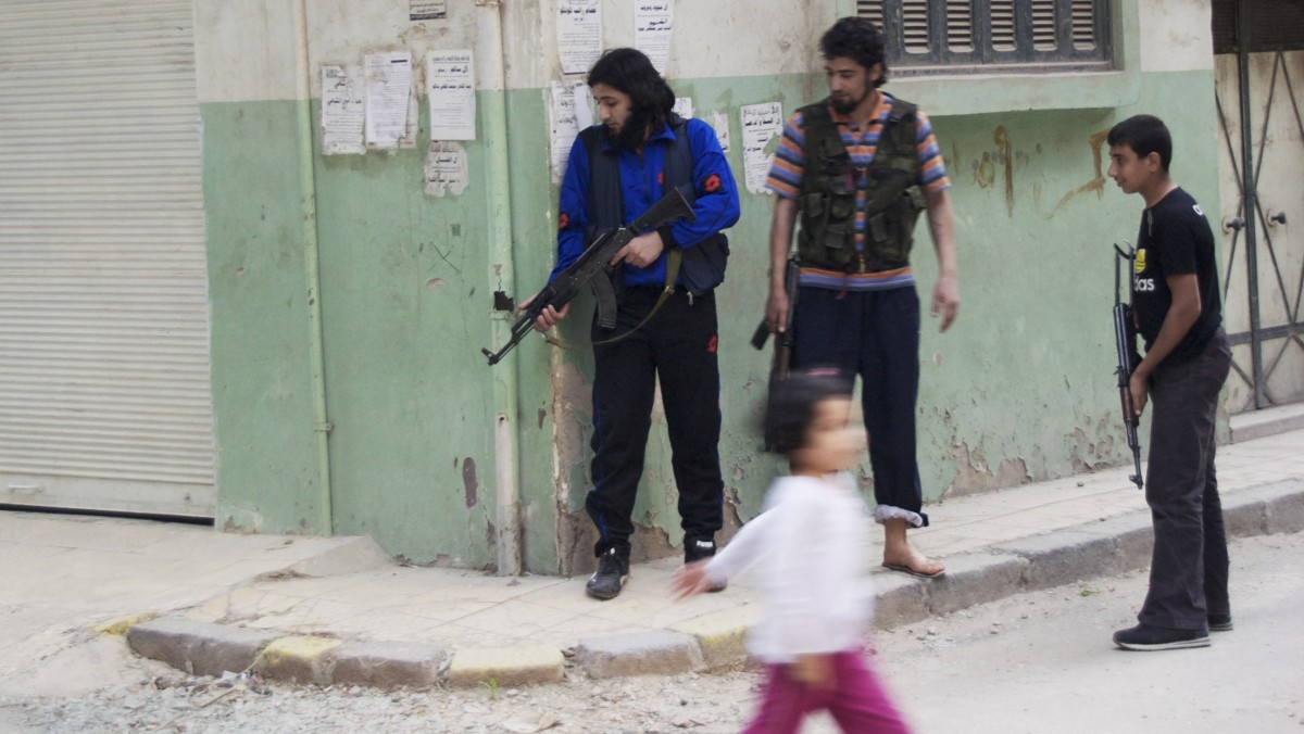 In this Monday, May 14, 2012 photo, a girl walks past Syrian rebels at Khaldiyeh neighborhood in Homs province, central Syria. The violence around the country is eroding an internationally brokered peace plan that many U.N. observers see as the last hope to calm the 14-month-old crisis. (AP Photo/Fadi Zaidan)