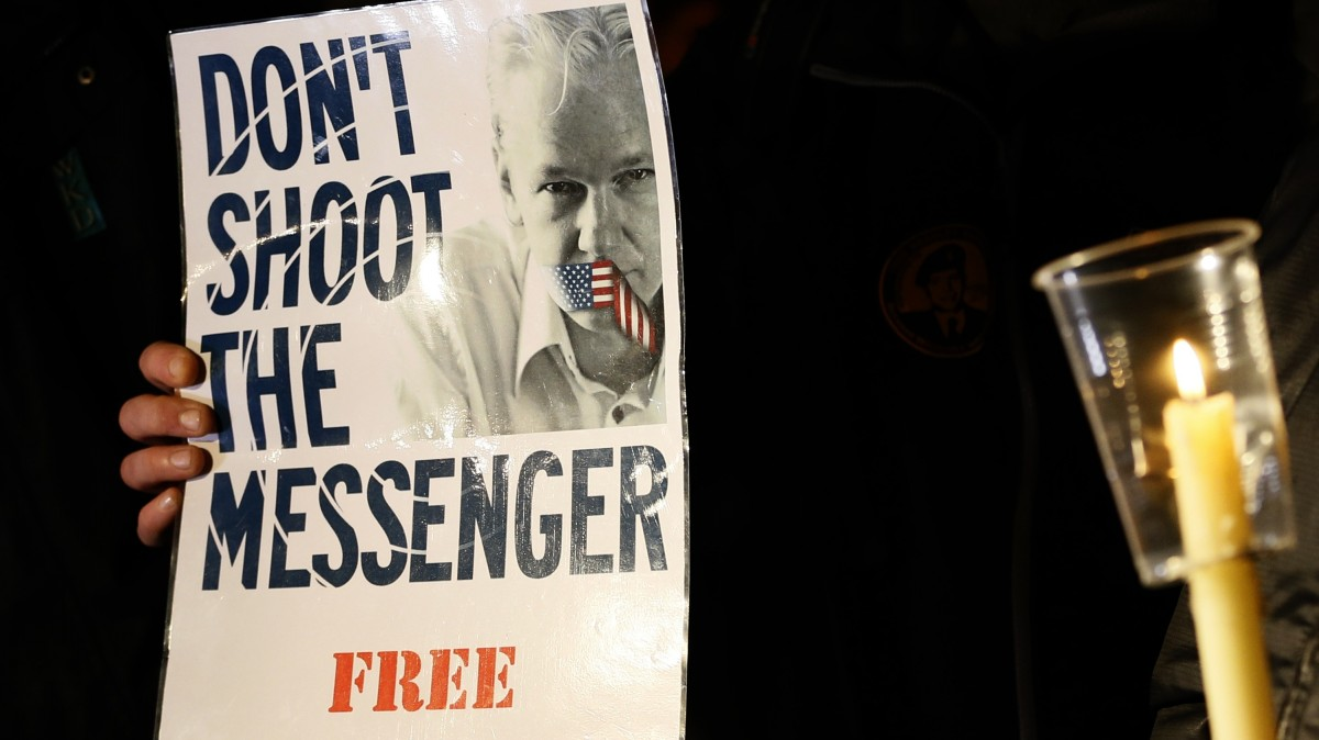 A supporter holds a banner as he waits for Julian Assange, founder of WikiLeaks to speak to the media and members of the public from a balcony at the Ecuadorian Embassy in London, Thursday, Dec. 20, 2012. (AP Photo/Kirsty Wigglesworth)