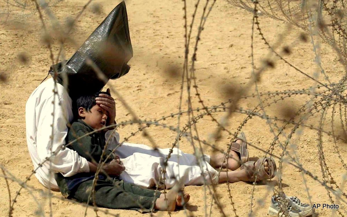 In this March 31, 2003 file photo, an Iraqi prisoner of war comforts his 4-year-old son at a regrouping center for POWs captured by the U.S. Army 101st Airborne Division near An Najaf, Iraq. The man was seized in An Najaf with his son by the U.S. military.