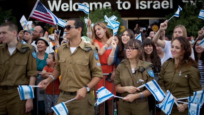 Israeli soldiers and relatives of new Jewish immigrants from the U.S. and Canada, wave Israeli flags to welcome them as they arrive at Ben Gurion airport near Tel Aviv, Israel, Tuesday, July 23, 2013.
