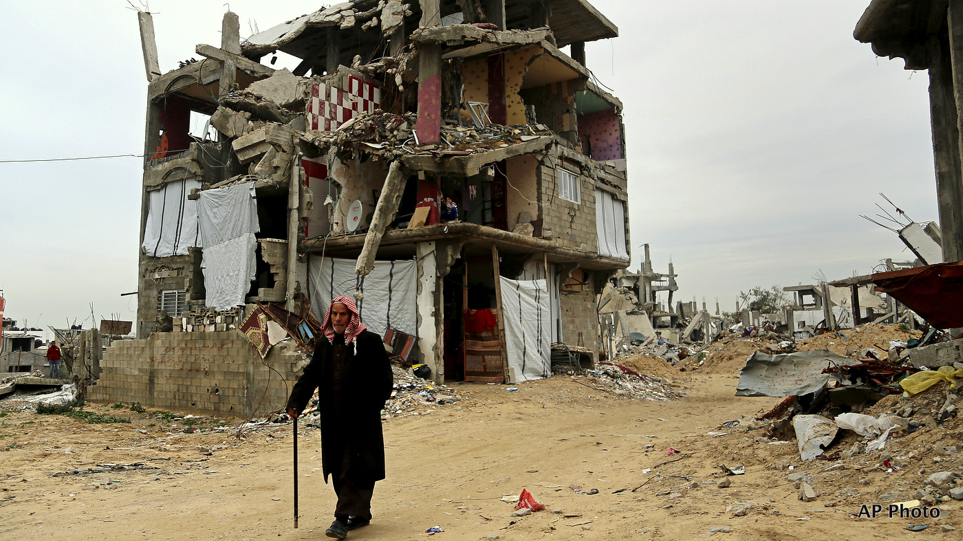 An elderly Palestinian walks past a destroyed  building in Gaza