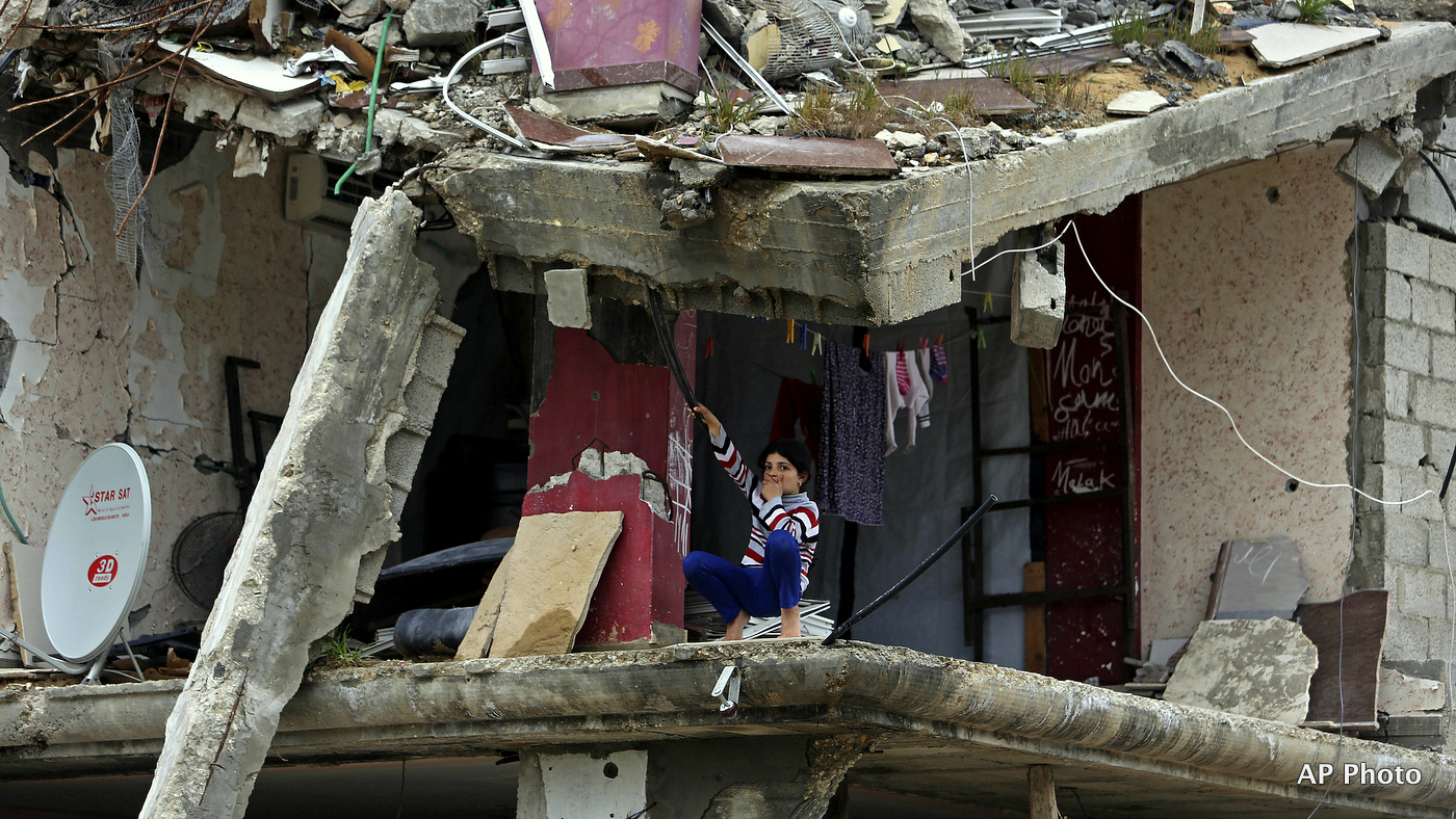 A Palestinian girl sits inside a room of her family's building which was damaged in last summer's Israel-Hamas war, in the Shijaiyah neighborhood of Gaza City, northern Gaza Strip, Monday, Feb. 23, 2015.