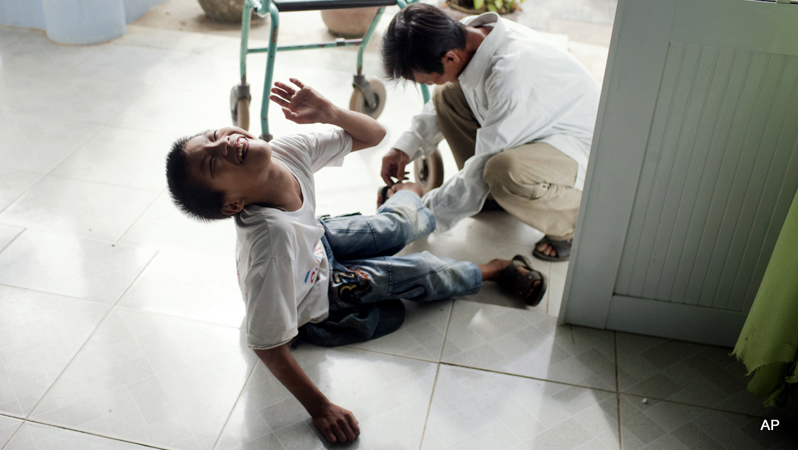In this photo taken on Wednesday, Aug. 8, 2012, Le Van Tam, 14, is picked up by his father at a rehabilitation center in Danang, Vietnam. The children were born with physical and mental disabilities that the center's director says were caused by their parents' exposure to the chemical dioxin in the defoliant Agent Orange. On Thursday, the U.S. for the first time will begin cleaning up leftover dioxin that was stored at the former military base that's now part of Danang's airport.  (AP Photo/Maika Elan)