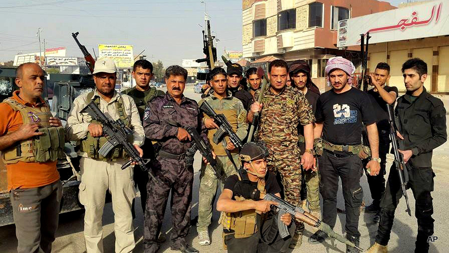 Iraqi security forces and Sunni tribal fighters pose for a photograph in central Ramadi, 70 miles (115 kilometers) west of Baghdad, Iraq, Thursday, April 16, 2015. Clashes between Iraqi forces and Islamic State militants pressing their offensive for Ramadi, the capital of western Anbar province, has forced more than 2,000 families to flee from their homes in the area, an Iraqi official said Thursday. The Sunni militants' push on Ramadi, launched Wednesday when the Islamic State group captured three villages on the city's eastern outskirts, has become the most significant threat so far to the provincial capital of Anbar.