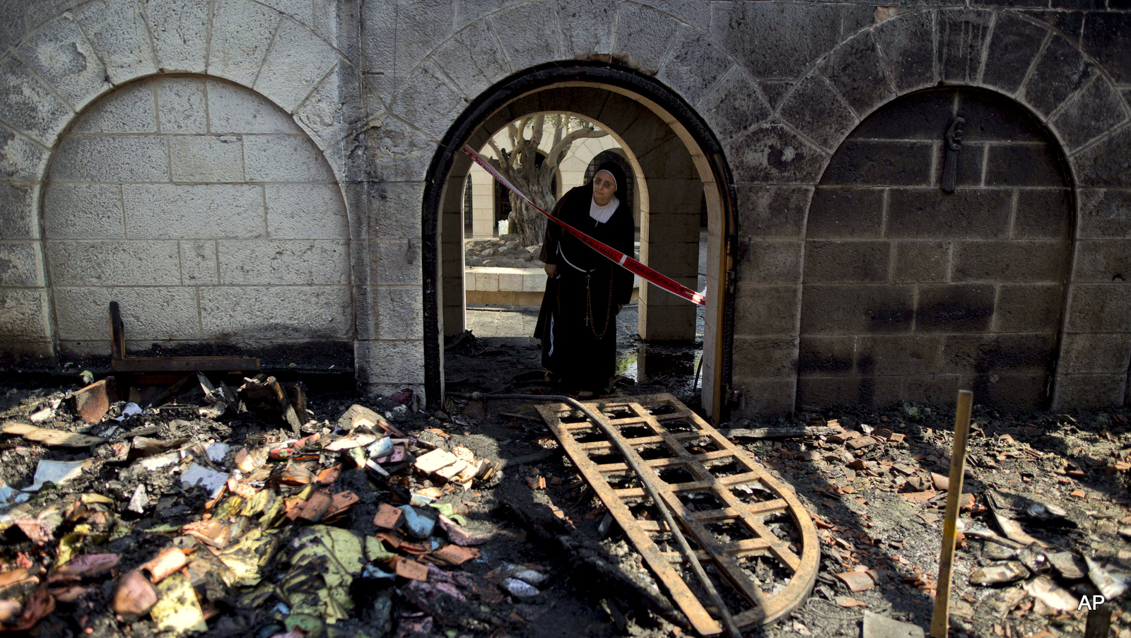 A nun looks at a heavily damaged Church of Multiplication after a fire broke out overnight near the Sea of Galilee in Tabgha, Israel