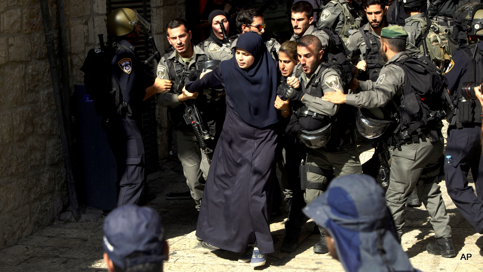 Israeli border police officers scuffle with Palestinian women in the Old City of Jerusalem on Sunday, July 26, 2015. Israeli police said they entered the al-Aqsa Mosque, the second-most holy site for Muslims, to
