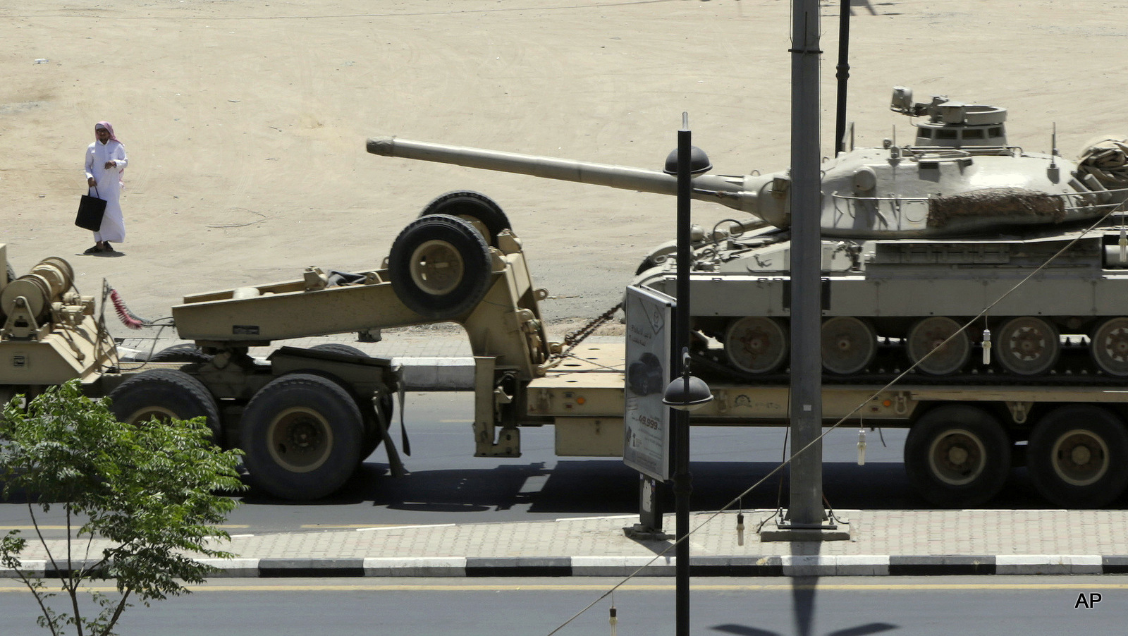 A Saudi man looks at an army tank being transported, in the city of Najran, Saudi Arabia, near the border with Yemen, Thursday, April 23, 2015.
