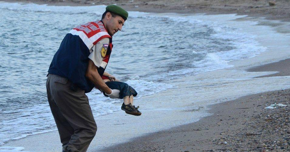 A paramilitary police officer carries the lifeless body of three-year-old Aylan Kurdi after he drowned when the boat he and his family members were in capsized near the Turkish resort of Bodrum early Wednesday, Sept. 2, 2015. (Photo: Nilüfer Demir/DHA)