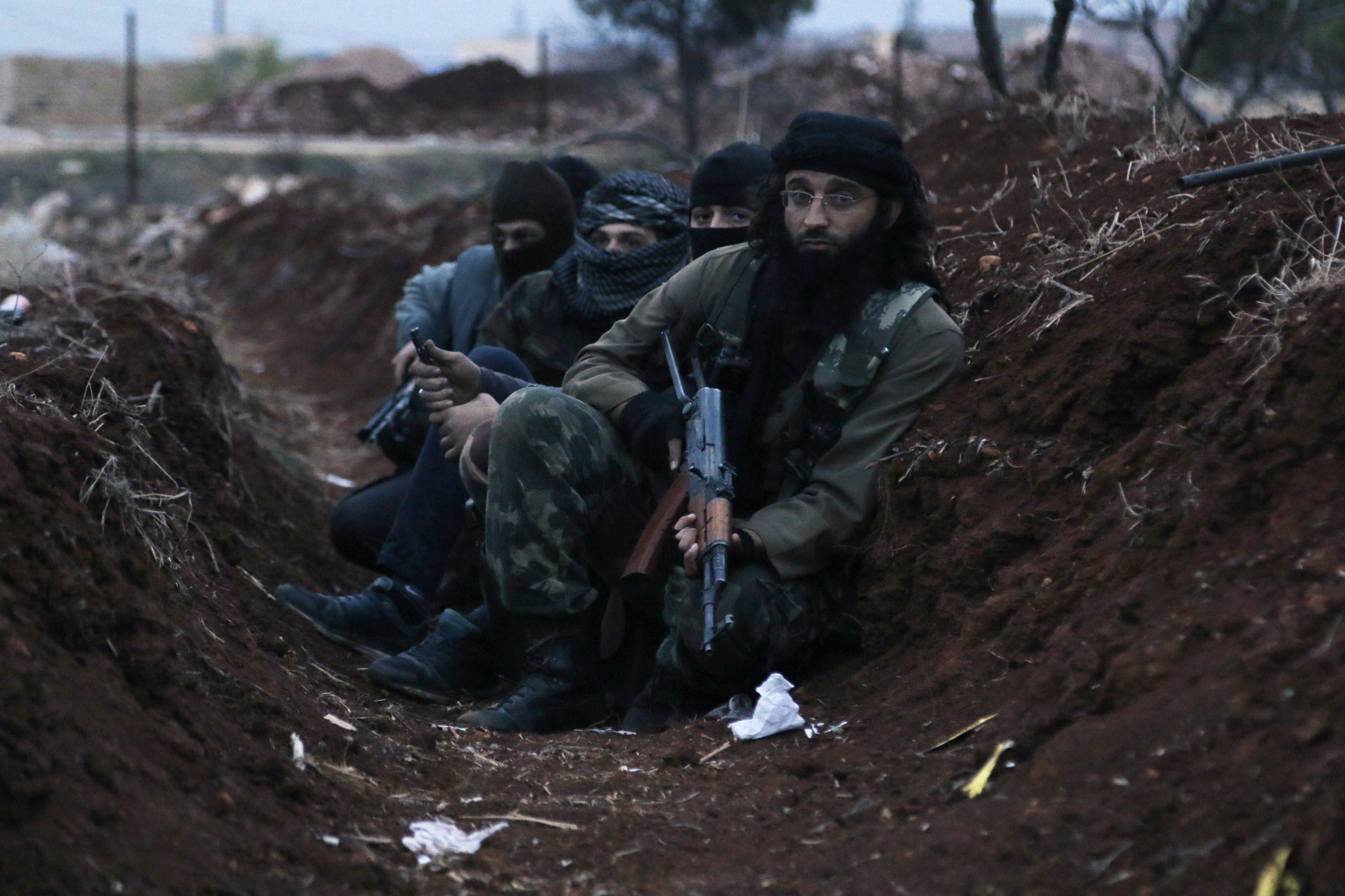 Members of al Qaeda's Nusra Front carry their weapons as they sit in a trench near al-Zahra village, north of Aleppo city, November 25, 2014. (REUTERS/Hosam Katan)