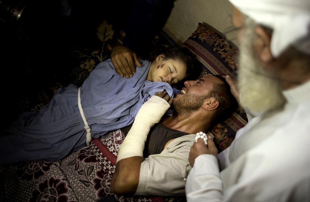The father of two-year-old, Rahaf Hassan, weeps as he holds her body after she and her 30-year-old mother pregnant mother, Noor Hassan, were killed in Israeli air strike in the Gaza Strip (AP/ Khalil Hamra)