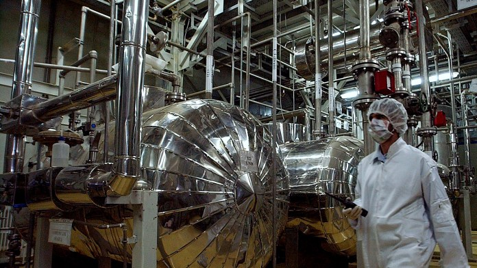 Wearing protective clothes, an Iranian security person walks at a part of the Uranium Conversion Facility, prior to the arrival of Iranian President Mohammad Khatami, just outside the city of Isfahan, 410 kilometers, south of the capital Tehran, Iran, Wednesday, March 30, 2005. The conversion facility in Isfahan reprocesses uranium ore concentrate, known as yellowcake, into uranium hexaflouride gas. The gas is then taken to Natanz and fed into the centrifuges for enrichment. (AP Photo/Vahid Salemi)