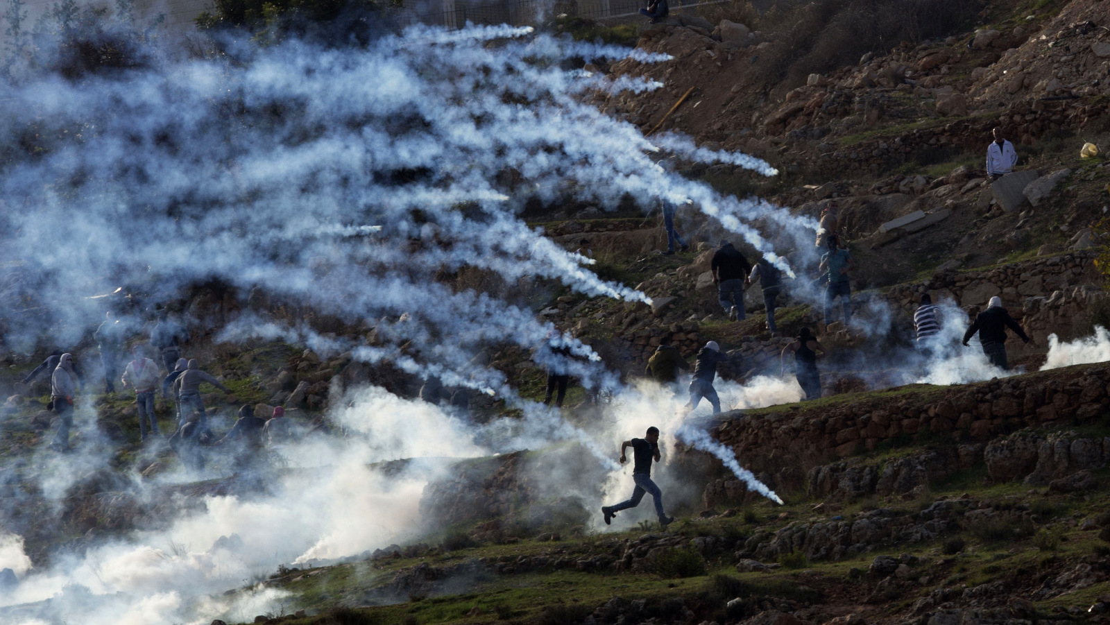 Palestinian protesters run from tear gas fired by Israeli troops during a protest of outside Ofer security prison in the occupied West Bank city of Ramallah. (AP Photo/Majdi Mohammed)