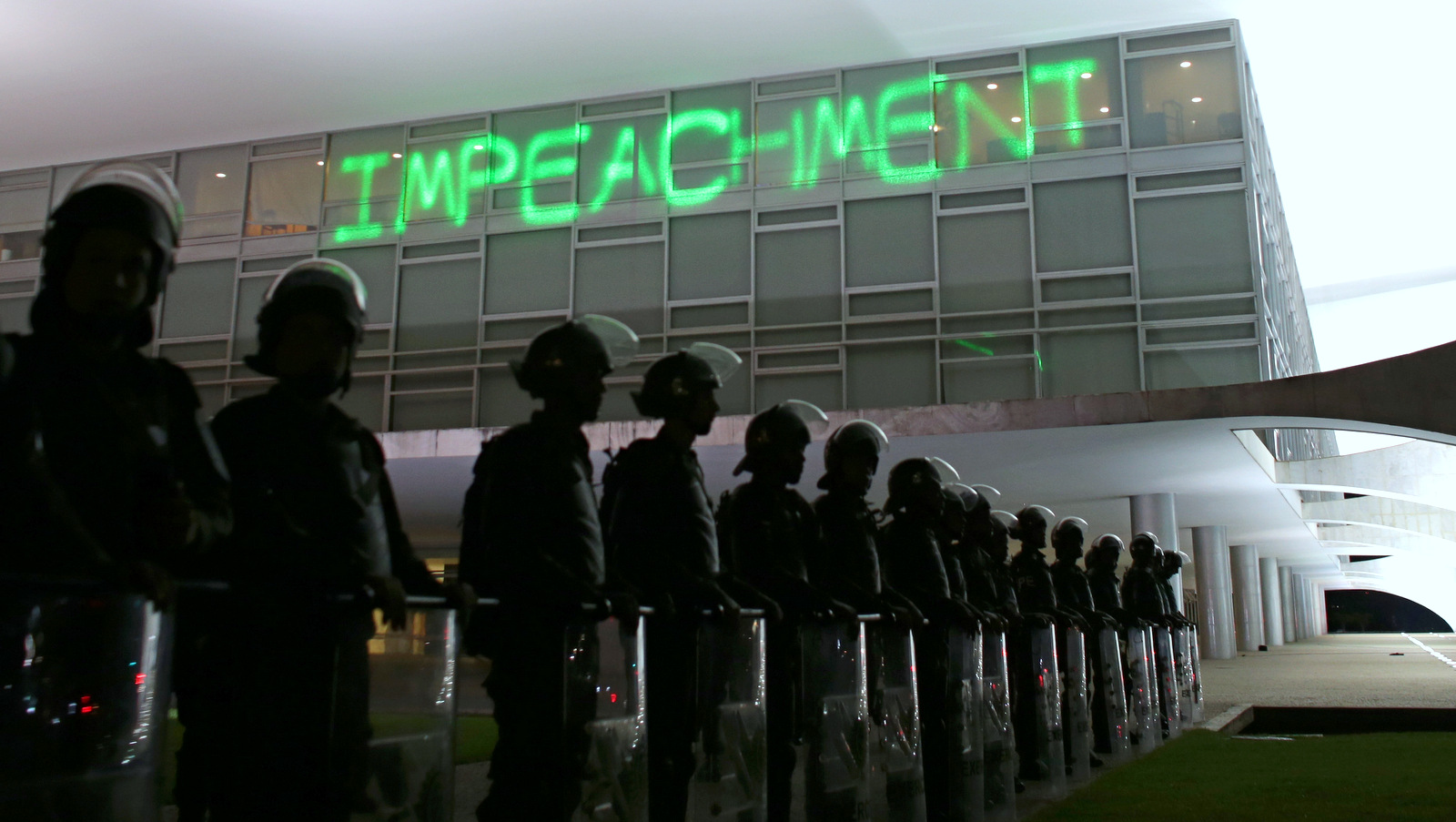 "Soldiers stand guard outside Planalto presidential palace where protesters have projected the word ""Impeachment"" on the building, as they call for the impeachment of Brazil's President Dilma Rousseff in Brasilia, Brazil, Monday, March 21, 2016. (AP/Eraldo Peres)"