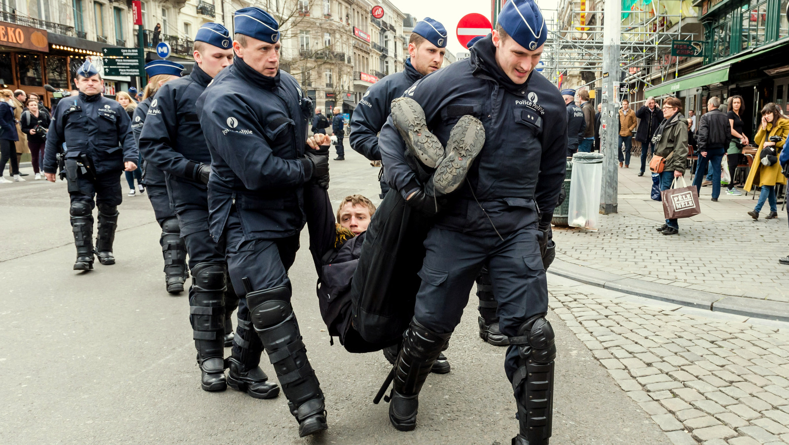 Policemen detain a man at the Place de la Bourse in Brussels, Belgium, after authorities banned all marches in Brussels. (AP Photo/Geert Vanden Wijngaert)