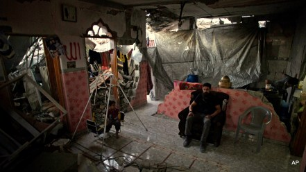 """Madi Hasanein, sits next to his son while he swings in what is left of their house in Tofah neighborhood of Gaza City. Gaza reconstruction is moving at a """"snail's pace"""" and at this rate, it would likely take 30 years to rebuild the extensive damage from Israel's war on Gaza senior U.N. official said."""