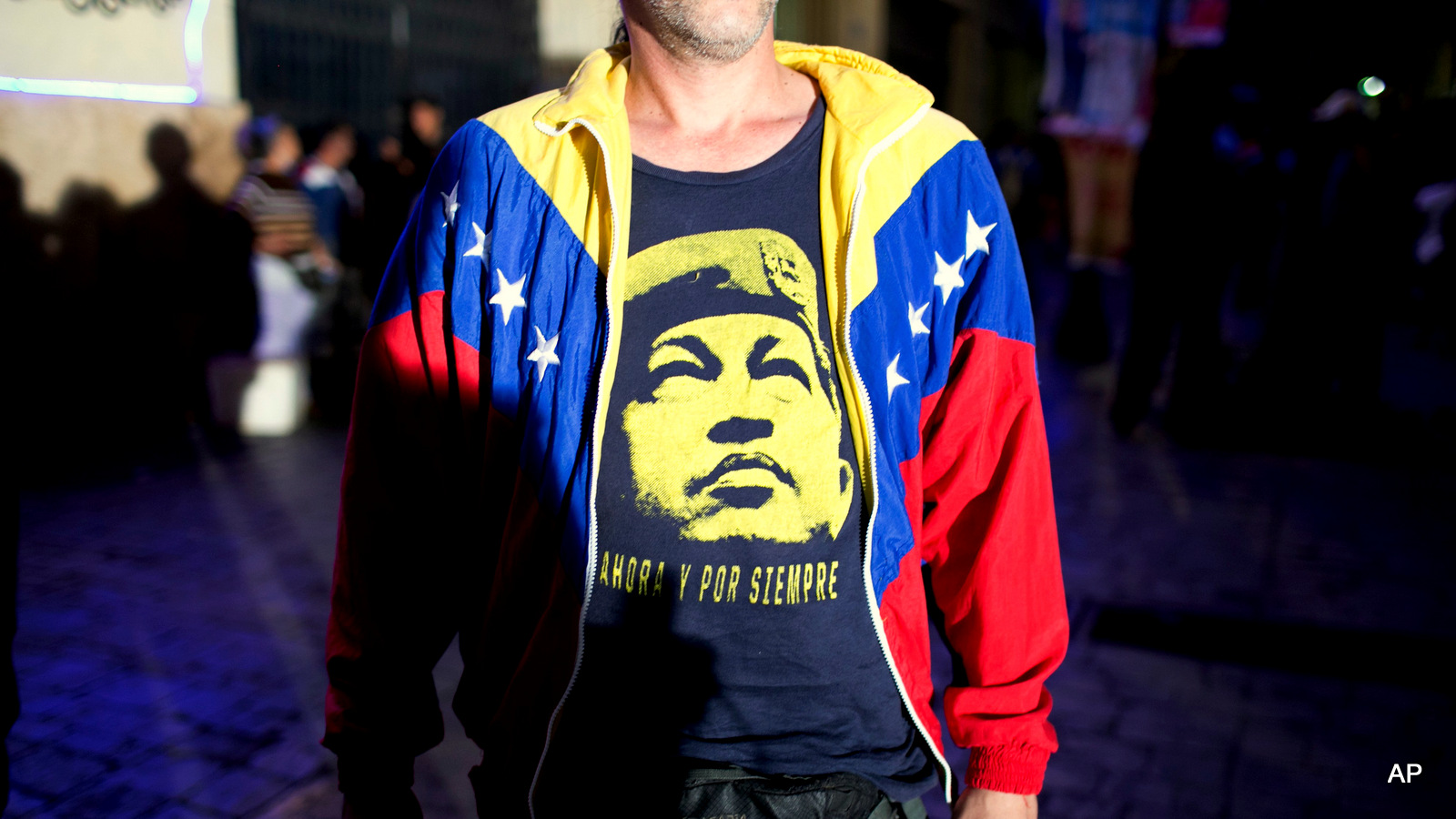 A pro-government supporter wears a T-Shirt with image of Venezuela's late President Hugo Chavez, as he waits for results during congressional elections in Caracas, Venezuela, Sunday, Dec. 6, 2015.