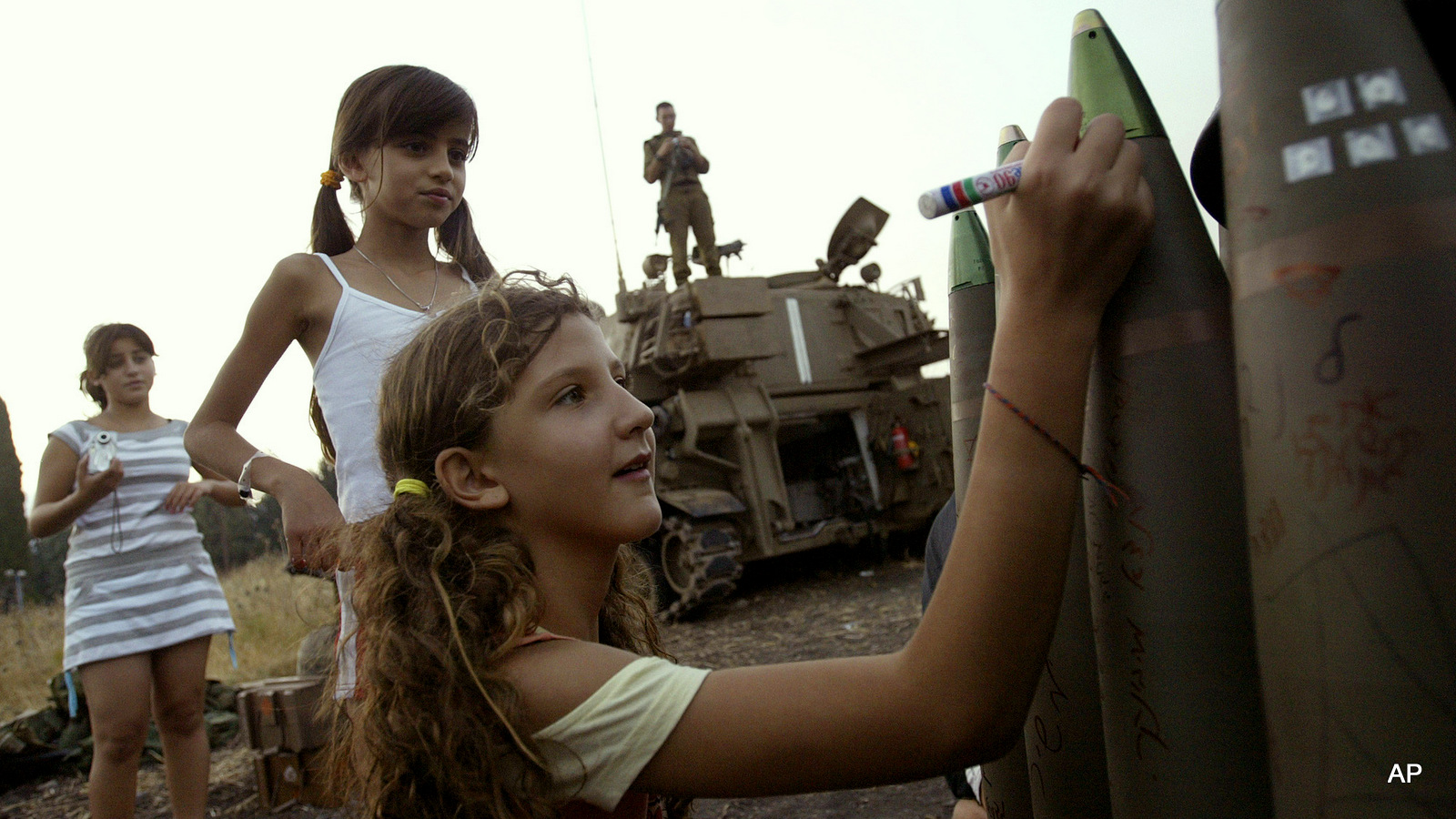 Israeli girls write messages on a bombs at a heavy artillery position near Kiryat Shmona, in northern Israel, next to the Lebanese border, Monday, July 17, 2006. (AP Photo/Sebastian Scheiner)