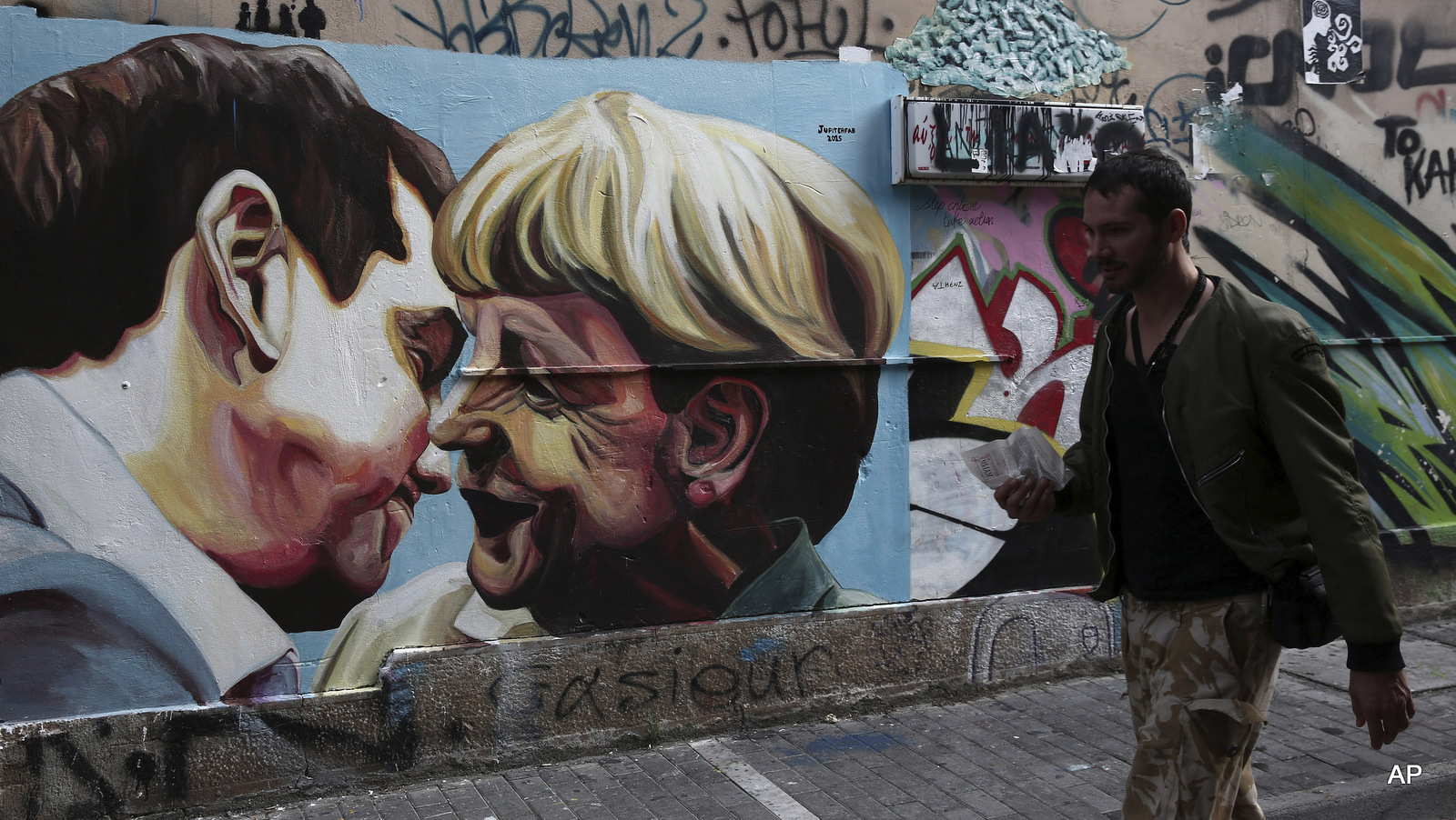 FILE - In this Sunday, Oct. 18, 2015 file photo, a man walks past street art depicting Greek Prime Minister Alexis Tsipras and German Chancellor Angela Merkel in Athens, Greece. Tsipras' decision to sign off on a bailout led to many in his left-wing Syriza party to quit in protest.