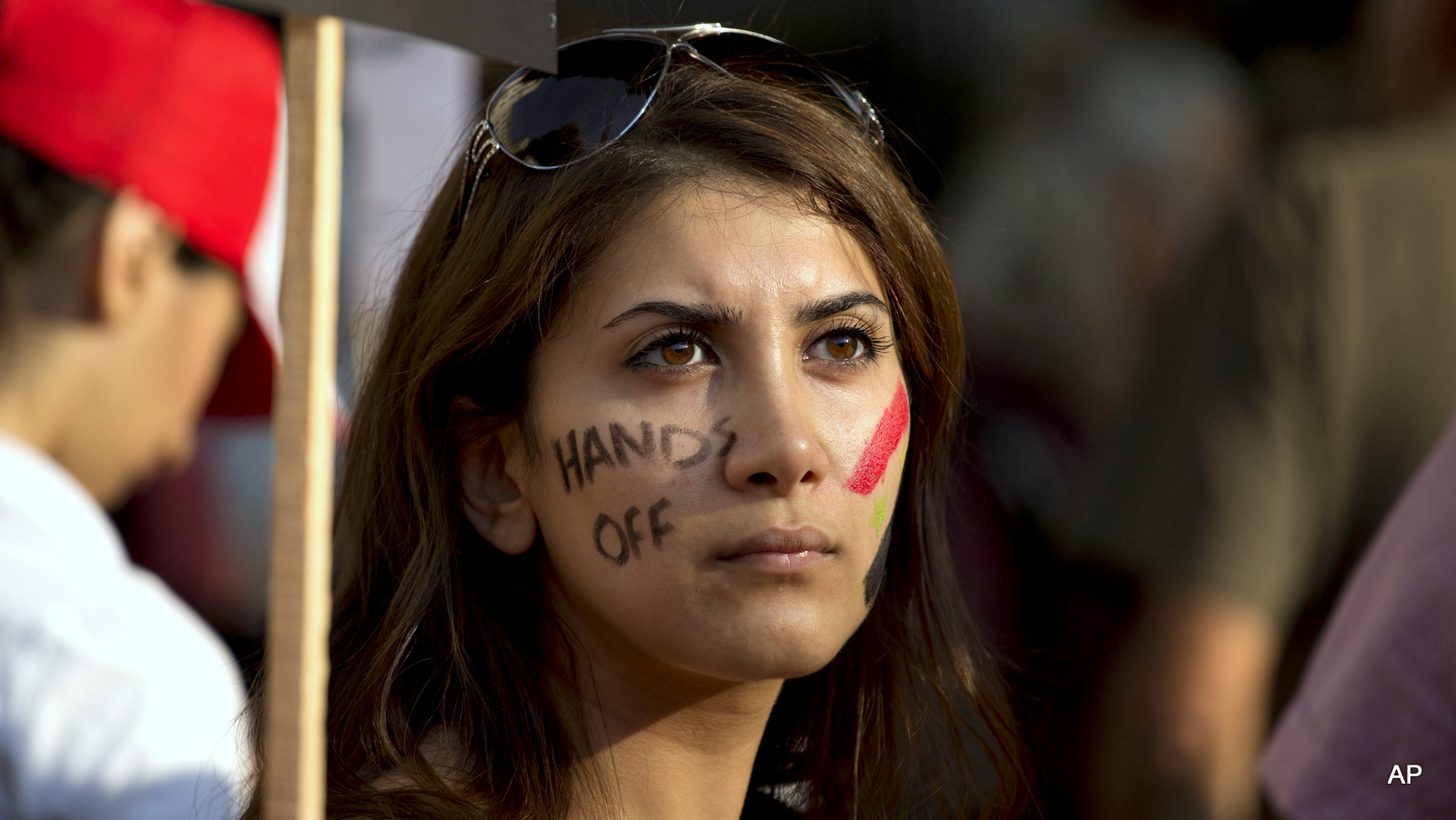 "A Syrian woman with the words ""hands off"" painted on her face takes part in a protest against US military action in Syria across the road from the entrance of Downing Street in London, Aug. 28, 2013."