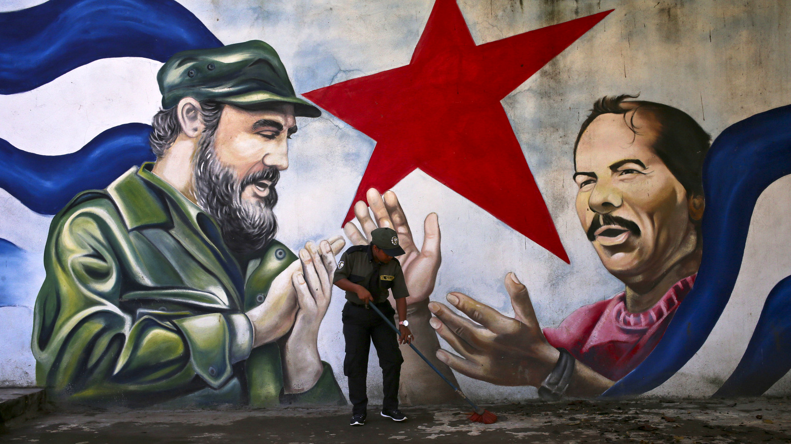 A woman sweeps the Cuba Plaza backdropped by a mural depicting Cuba's former President Fidel Castro and Nicaragua's President Daniel Ortega, in Managua, Nicaragua, Friday, Nov. 4, 2016. (AP Photo/Esteban Felix)