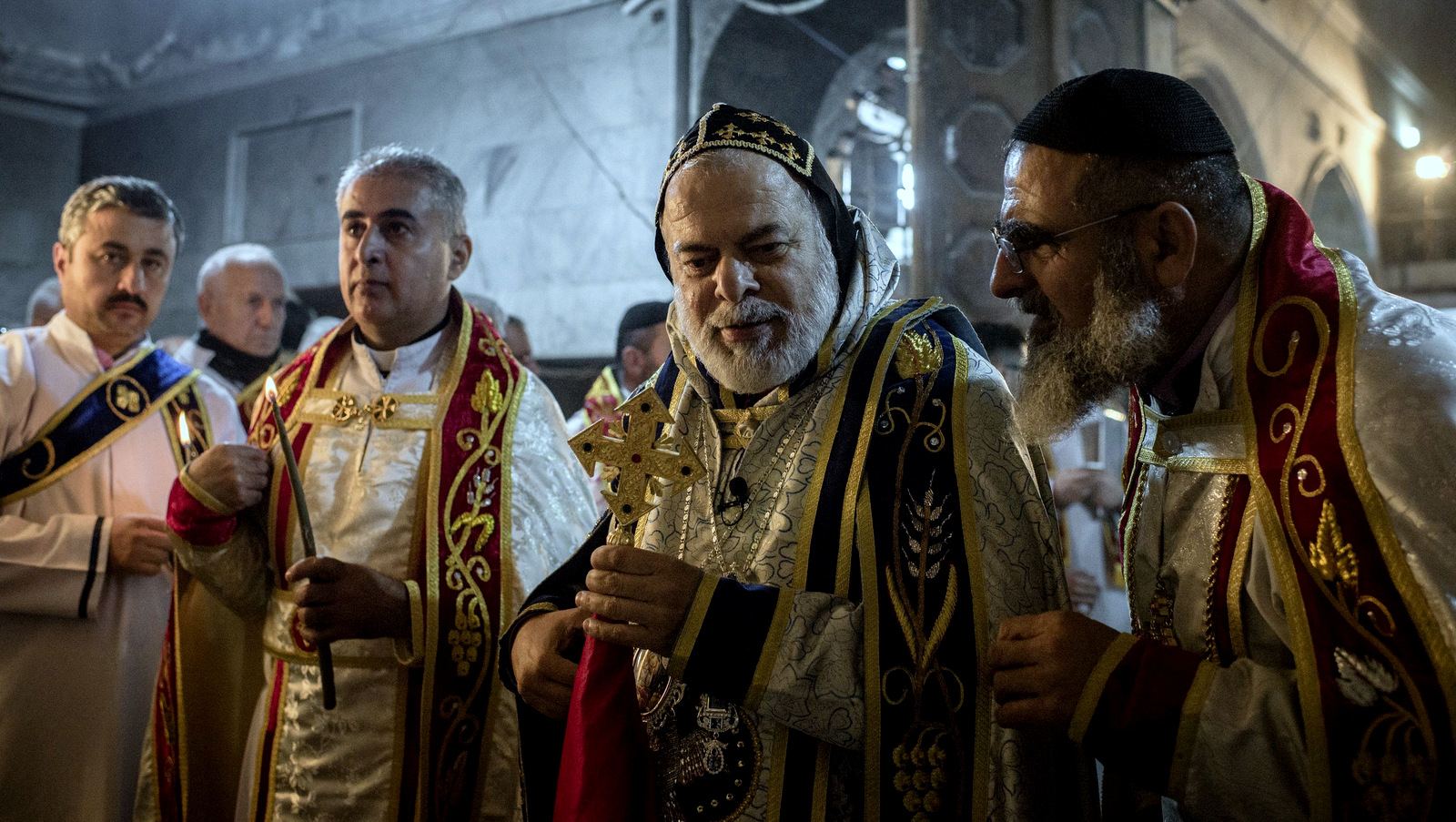 Priests lead a Christmas Eve's Mass in the Assyrian Orthodox church of Mart Shmoni, in Bartella, Iraq, Saturday, December 24, 2016. For the 300 Christians who braved rain and wind to attend the mass in their hometown, the ceremony provided them with as much holiday cheer as grim reminders of the war still raging on around their northern Iraqi town and the distant prospect of moving back home. Displaced when the Islamic State seized their town in 2014, they were bused into the town from Irbil, capital of the self-ruled Kurdish region, where they have lived for more than two years. (AP Photo/Cengiz Yar)