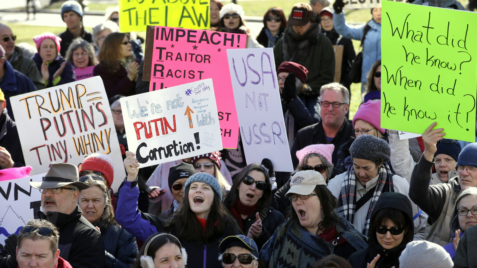 "Protesters hold placards and chant slogans during a demonstration called ""Emergency Rally to Stand for Democracy,"" Sunday, Feb. 26, 2017, in Boston. Demonstrators called for an investigation into what they describe as the possible involvement of Russian officials in the campaign of then presidential candidate Donald Trump in the Nov. 2016 electio"