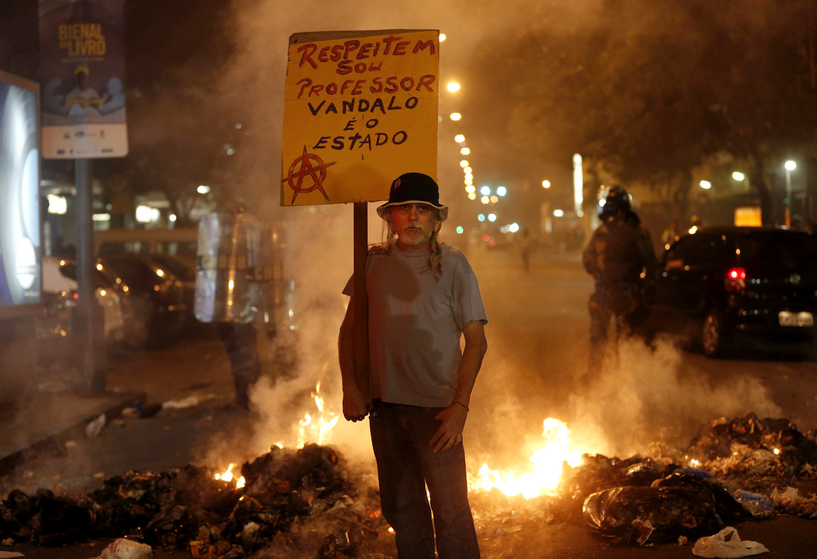 "A man holds a sign that reads in Portuguese ""Respect, I'm a teacher, the vandal is the state"" at a burning barricade set up by protesters in Rio de Janeiro, Brazil. (AP/Silvia Izquierdo)"
