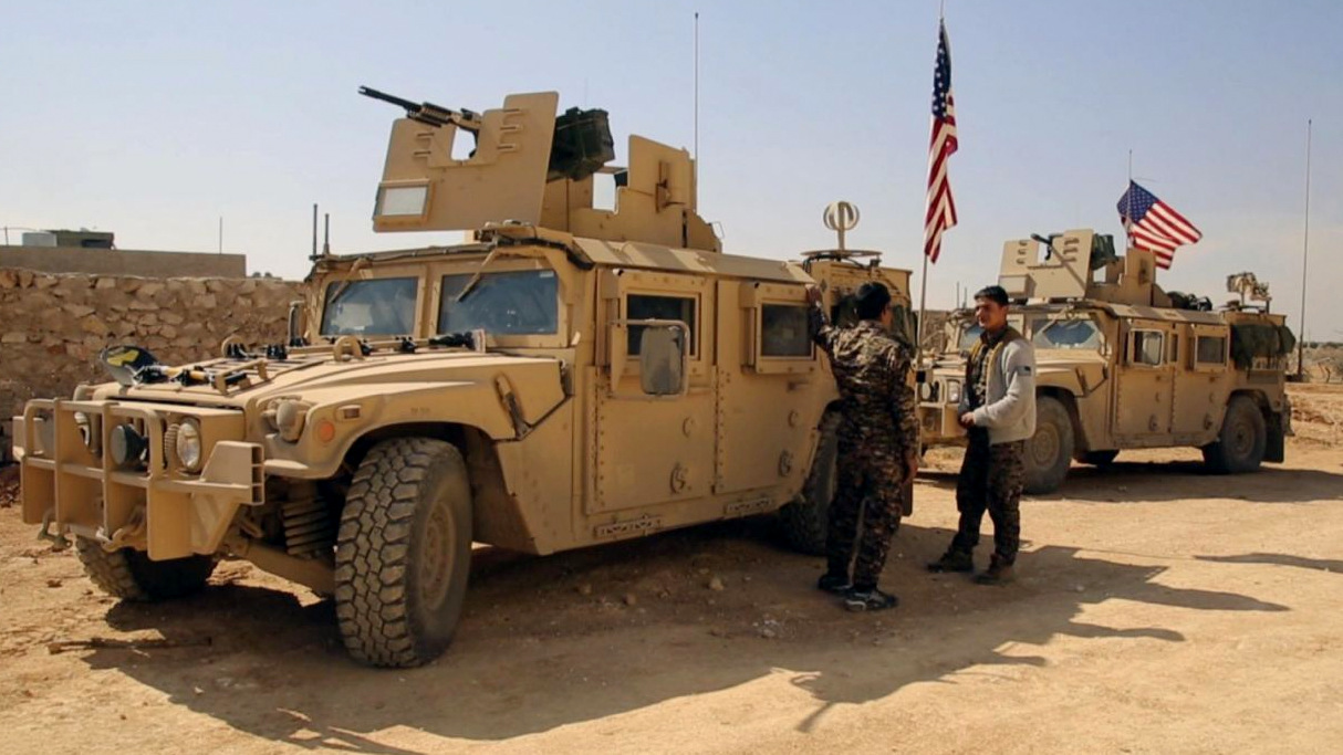 Syrian Rebel Fighters stand near U.S military vehicles on the outskirts of the Syrian town, Manbij, Syria, March 7, 2017. (Arab 24 via AP)