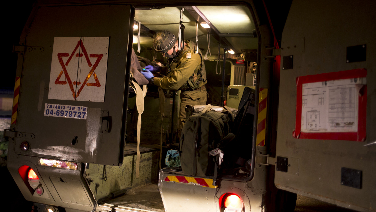 In this Thursday, April 6, 2017 photo made in Israeli controlled Golan Heights, Israeli military medics assist wounded Syrians. Seven wounded Syrians crossed into Israeli controlled Heights Thursday night have received immediate treatment and were hospitalized later on. They are the latest group of Syrian fighters receiving free medical care through an Israeli military program operating since 2013. (AP/Dusan Vranic)