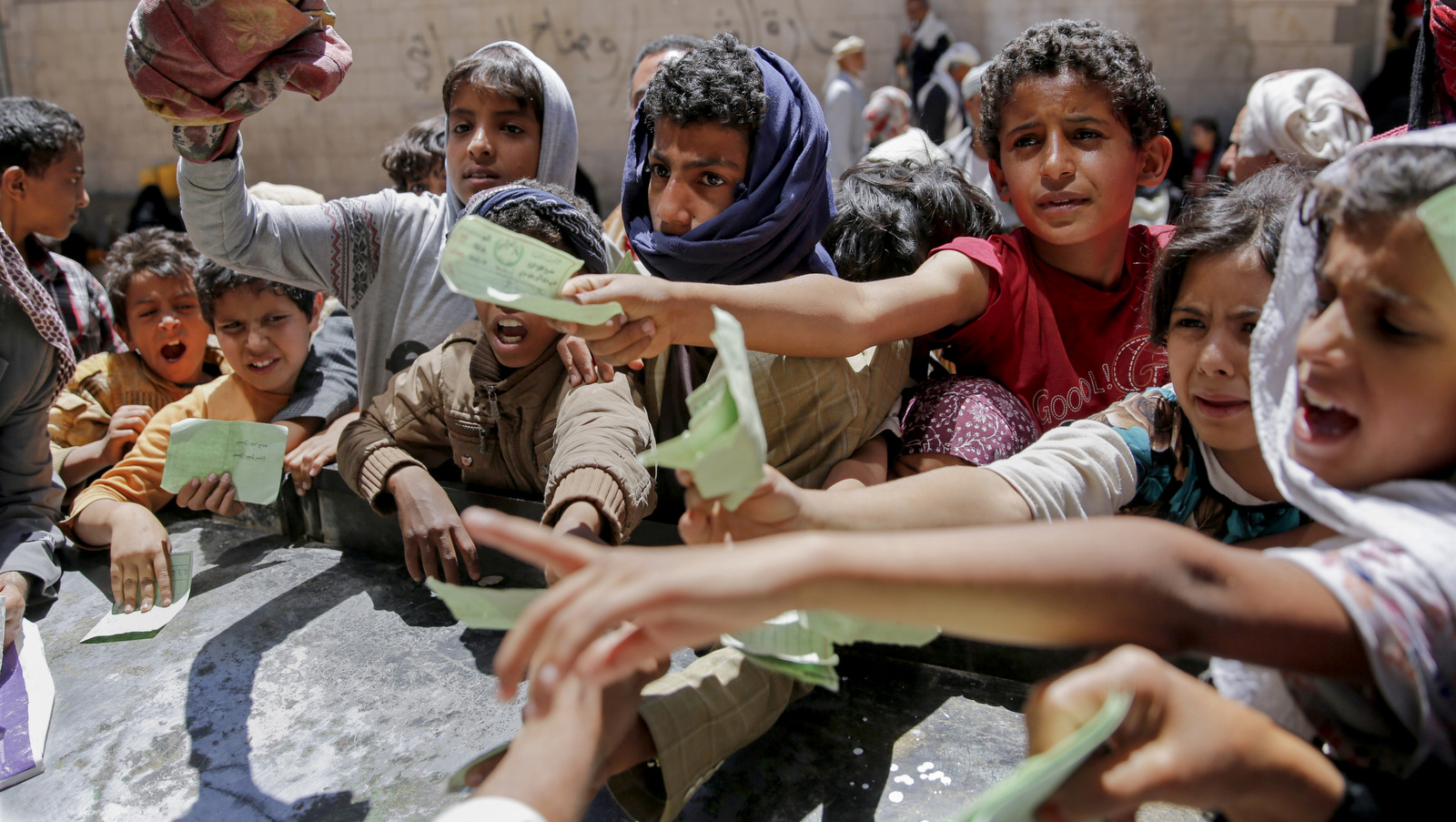 Yemenis present documents in order to receive food rations provided by a local charity, in Sanaa, Yemen, Thursday, April, 13, 2017. A Saudi-led coalition launched a campaign in support of Yemen's internationally recognized government in March 2015. The war has pushed the Arab world's poorest country to the brink of famine. (AP/Hani Mohammed)