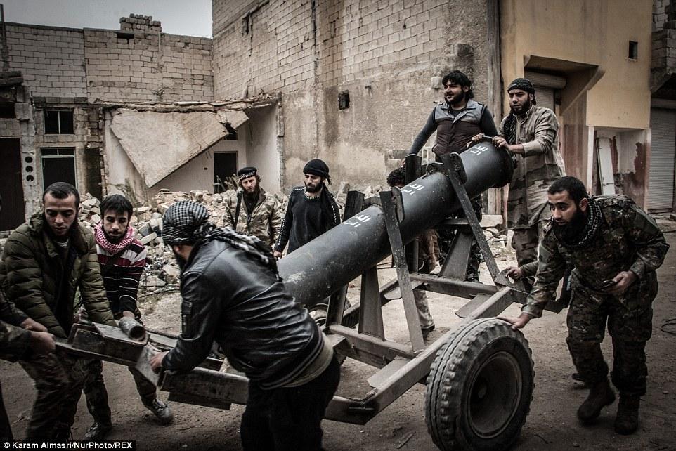 """Mitglied der Freien syrischen Armee bereit eine hausgemachte Waffe als """"Höllenkanone"""" in den Ruinen der Stadt Aleppo bekannt."""