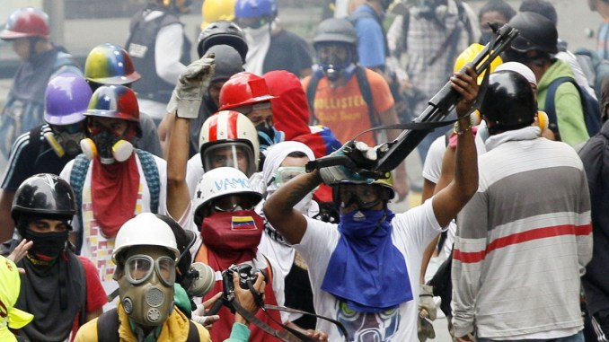 An anti-government protester wields a shotgun taken from security forces during clashes in Caracas, Venezuela, May 8, 2017. The protest movement has drawn masses of people into the streets nearly every day since March, has left some three dozen dead. (AP/Ariana Cubillos)