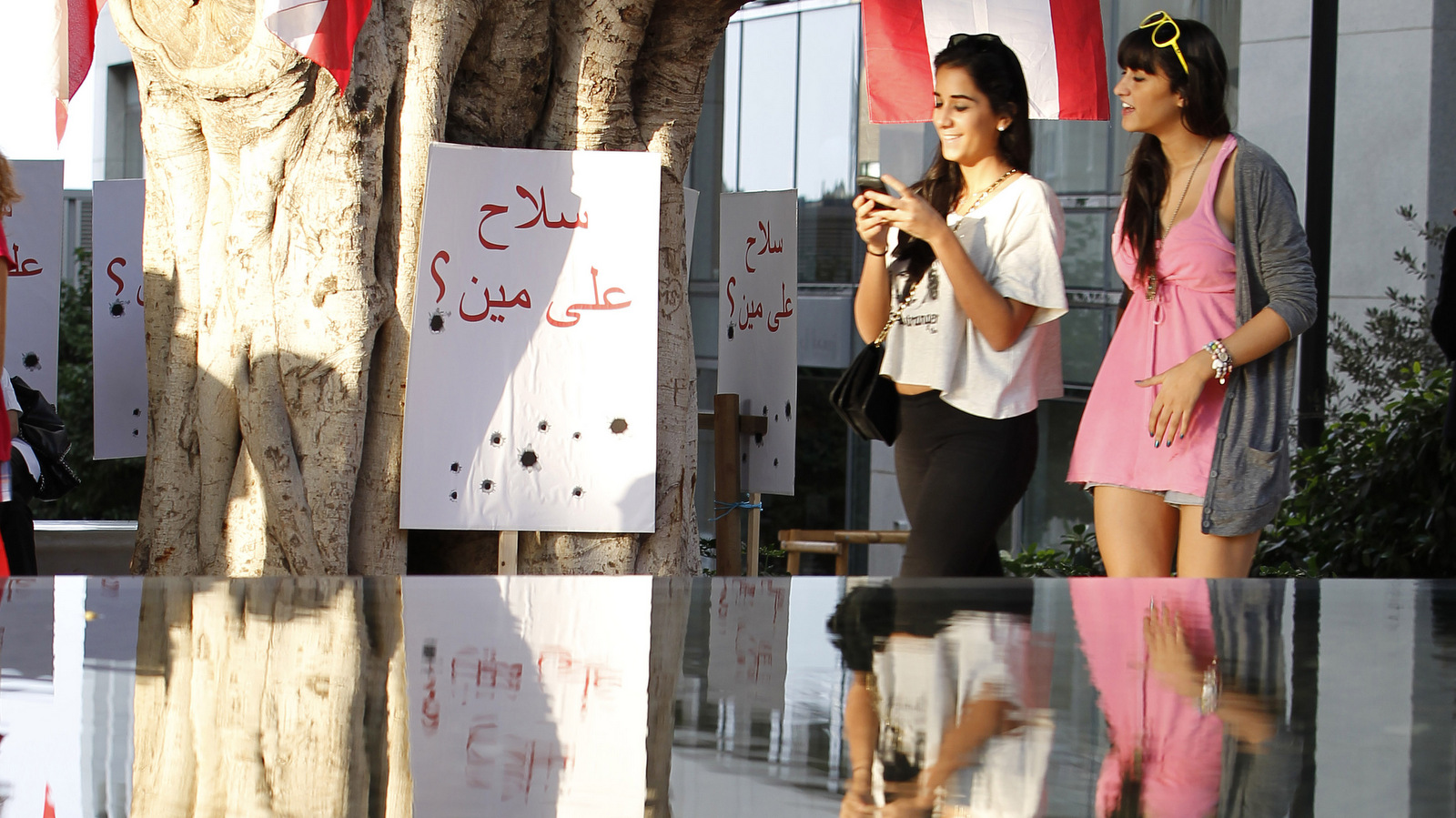 Lebanese activists stand near a banner that reads in Arabic: