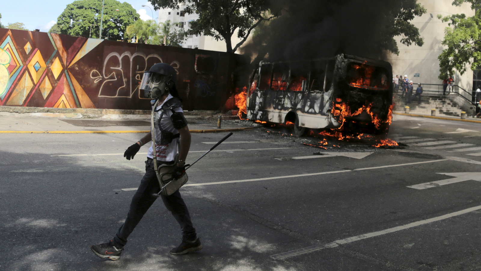 A protester wearing a gas mask and carrying a golf club walks to join fellow protesters, past a burning public transportation bus in Caracas, Venezuela, May 13, 2017. The anti-government protest movement that has drawn masses of people into the streets nearly every day since March, continued on Saturday. (AP/Fernando Llano)