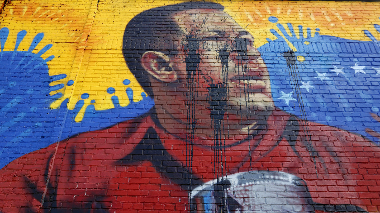 A mural featuring an image of former Venezuelan President Hugo Chavez was defaced in the Bronx borough of New York, Tuesday, May 9, 2017. (AP/Seth Wenig)