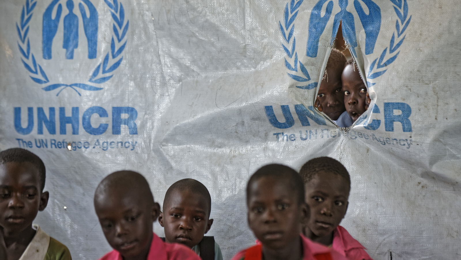 In this photo taken Wednesday, June 7, 2017, children look through a tear in the tarpaulin tents that serve as extra classrooms, for a mixed class of South Sudanese refugee children and Ugandan children, at the Ombechi Primary School in Bidi Bidi refugee settlement, northern Uganda. There is an urgent need to educate children in this overcrowded settlement that is home to over 270,000 refugees from South Sudan's civil war, despite them often having to walk long distances to the nearest school, funding shortages and a reduction in food rations for some refugees. (AP/Ben Curtis)