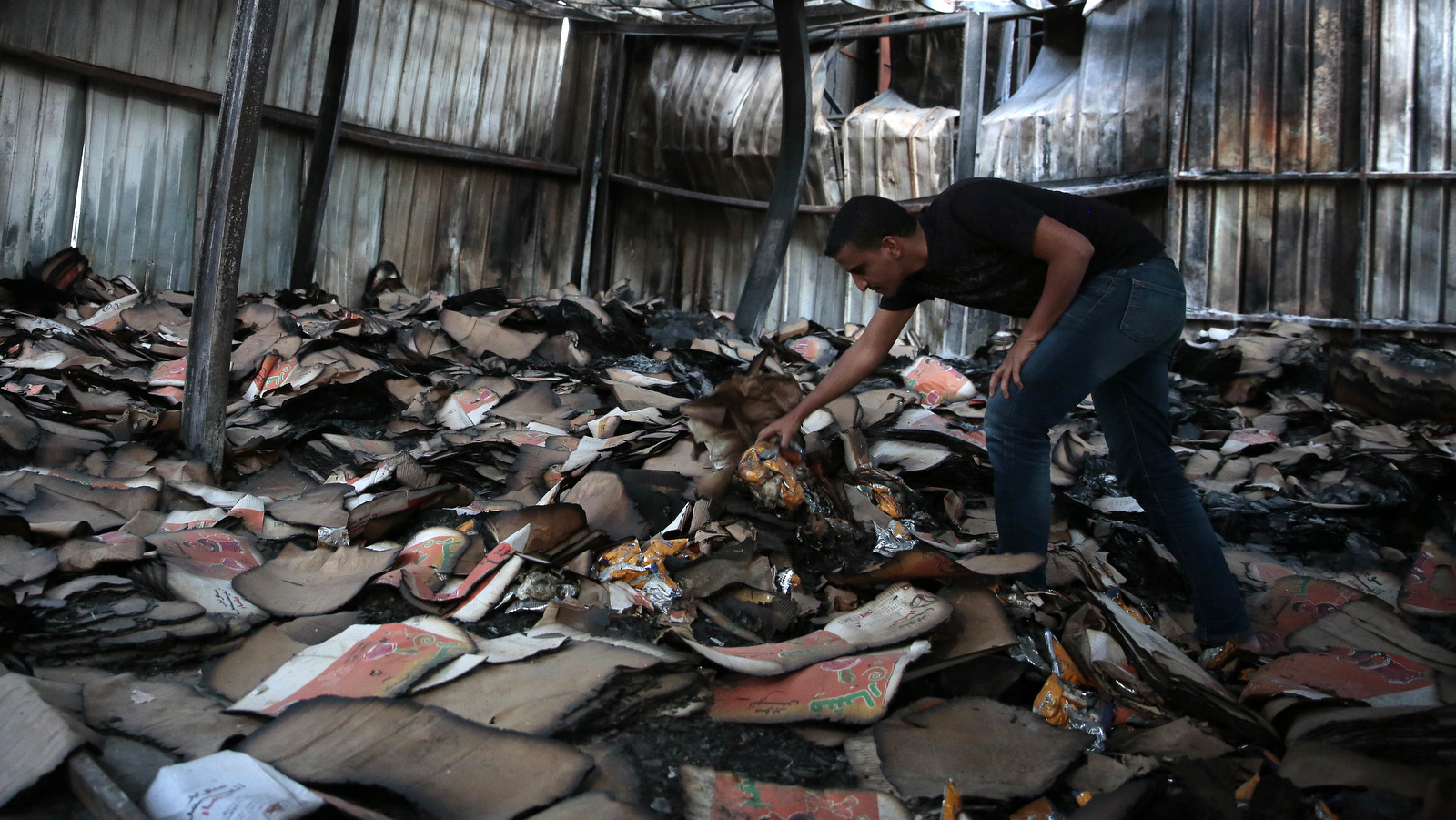 A man inspects a food factory hit by Saudi-airstrikes, in Sanaa, Yemen. Human rights experts say there has been a pattern by the Saudi-coalition in failing to distinguish between civilian and military targets and disregarding the likelihood of civilian casualties, likely amounting to war crimes. (AP/Hani Mohammed)