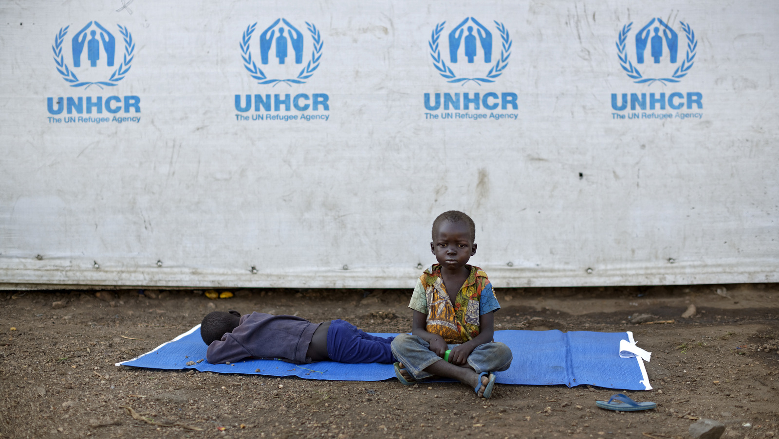 A South Sudanese refugee sits on a mat outside a communal tent with his brother at the Imvepi reception center, where newly arrived refugees are processed in northern Uganda Friday, June 9, 2017. (AP/Ben Curtis)