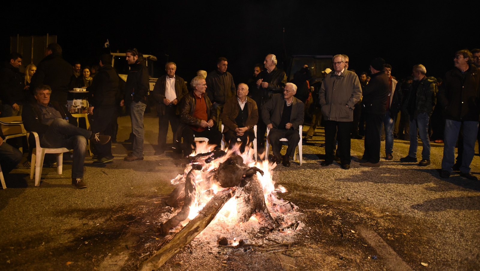 In this Feb. 2, 2016 photo farmers stand behind a makeshift fire in front of tractors, near Kerdilia, Greece. Combine a rapidly aging population, a depleted work force and leaky finances and any country's pension system would be in trouble. For debt-hobbled, unemployment-plagued Greece, it's a nightmare.(AP/Giannis Papanikos)