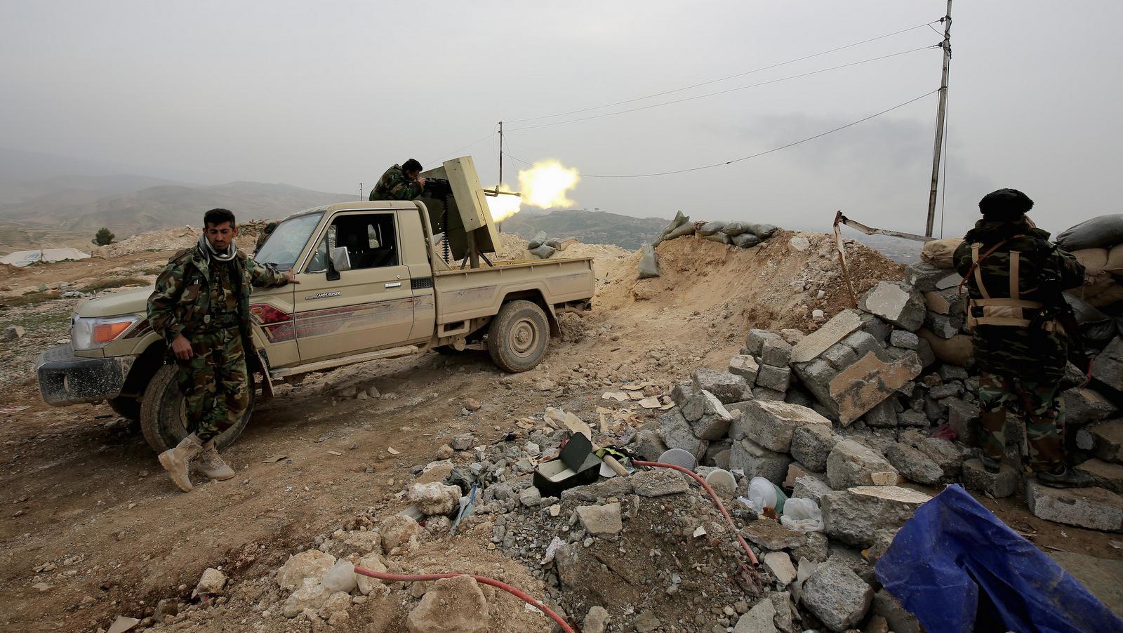 Well-armed Kurdish Peshmerga fighters fire a weapon toward the strategic town of Sinjar, northern Iraq. . (AP/Bram Janssen)