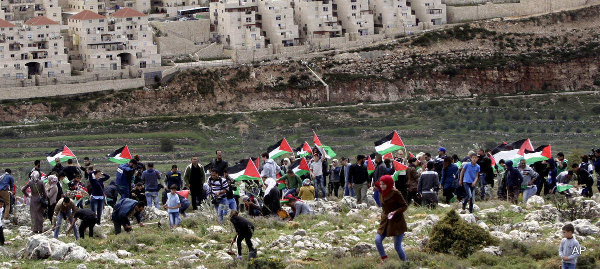 Palestinian protesters carry national flags and plant olive trees facing the Israeli settlement of Beitar Illit during a protest marking Land Day, in the village of Wadi Fukin, near the West Bank city of Bethlehem, March 30, 2015.